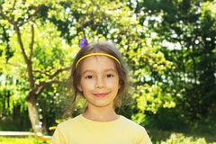 Cute smiling little girl on background of city park. Stock Photography