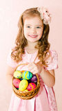 Cute smiling little girl with basket full of colorful easter egg Stock Photography
