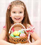 Cute smiling little girl with basket full of easter eggs Stock Photo