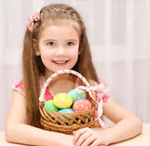 Cute smiling little girl with basket full of easter eggs Stock Images