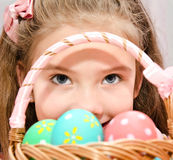 Cute smiling little girl with basket full of easter eggs Royalty Free Stock Images