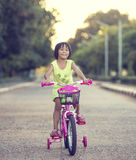 Cute smiling little girl with bicycle. On road Stock Photos