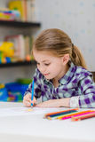 Cute smiling little girl with blond hair sitting at table and drawing with multicolored pencils. Cute smiling little girl with blond hair sitting at white table royalty free stock photo