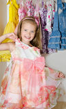 Cute smiling little girl chooses a dress from the wardrobe Royalty Free Stock Photography