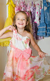 Cute smiling little girl chooses a dress from the wardrobe Stock Image