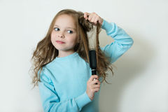 Cute smiling little girl combing her hair comb makes hair. Facial expression Royalty Free Stock Image