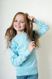 Cute smiling little girl combing her hair comb makes hair Royalty Free Stock Photos