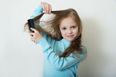 Cute smiling little girl combing her hair comb makes hair Royalty Free Stock Images