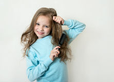 Cute smiling little girl combing her hair comb makes hair Royalty Free Stock Image