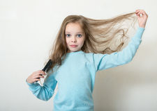 Cute smiling little girl combing her hair comb makes hair. Light background Stock Image