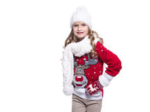Cute smiling little girl with curly hairstyle wearing knitted sweater, scarf, hat and gloves isolated on white background. Royalty Free Stock Image