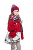 Cute smiling little girl with curly hairstyle wearing knitted sweater, scarf, hat and gloves with skates isolated on white. Royalty Free Stock Images