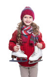 Cute smiling little girl with curly hairstyle wearing knitted sweater, scarf, hat and gloves with skates isolated on white. Stock Photos