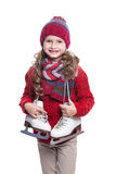 Cute smiling little girl with curly hairstyle wearing knitted sweater, scarf, hat and gloves with skates isolated on white Stock Image