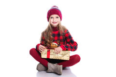 Cute smiling little girl with curly hairstyle wearing knitted sweater, scarf and hat holding christmas gift isolated on white Stock Image