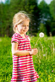 Cute smiling little girl with dandelion in her hands makes wish Royalty Free Stock Image