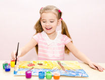 Cute smiling little girl drawing with paint and paintbrush Royalty Free Stock Photography