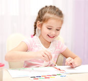 Cute smiling little girl drawing with paint and paintbrush Royalty Free Stock Image