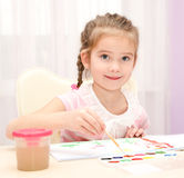 Cute smiling little girl drawing with paint Royalty Free Stock Images