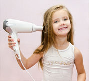 Cute smiling Little girl dries hair Stock Images