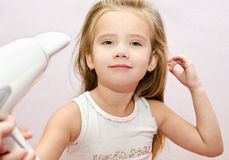 Cute smiling Little girl dries hair Stock Photos