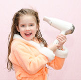 Cute smiling little girl dries hair Royalty Free Stock Image