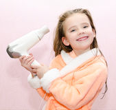 Cute smiling little girl dries hair Stock Photo