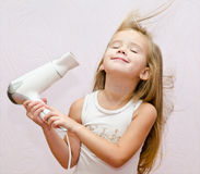 Cute smiling Little girl dries hair Royalty Free Stock Photos