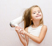 Cute smiling Little girl dries hair Stock Photo