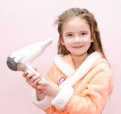 Cute smiling little girl dries hair Royalty Free Stock Photo