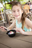 Cute smiling little girl eating a delicious bowl of ice cream at an outdoor cafe Royalty Free Stock Photo