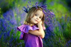 Cute smiling little girl with flower wreath on the meadow at the farm. Portrait of adorable small kid outdoors. Little girl on lavender field. Portrait of a Royalty Free Stock Images