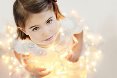 Cute, smiling little girl with glowing Christmas lights stock photography