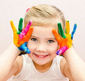 Cute smiling little girl with hands in paint Royalty Free Stock Image