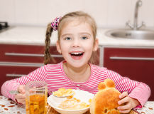 Cute smiling little girl having breakfast cereals with milk Stock Photos