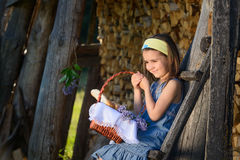 Cute smiling little girl holding a basket of flowers. Portrait in profile. stock image