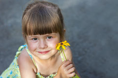 Cute smiling little girl holding yellow flower Stock Images