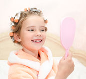 Cute smiling little girl looking at the mirror Royalty Free Stock Image
