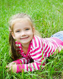 Cute smiling little girl lying in grass on the meadow Stock Photos
