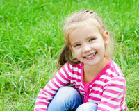 Cute smiling little girl lying in grass on the meadow Stock Image