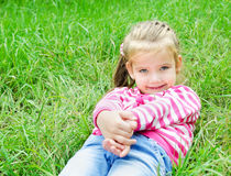 Cute smiling little girl lying in grass on the meadow Stock Images