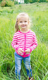 Cute smiling little girl lying in grass on the meadow Stock Photography