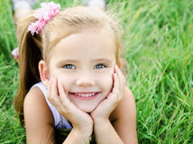 Cute smiling little girl lying in grass on the meadow Royalty Free Stock Image