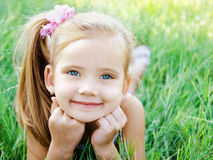 Cute smiling little girl lying in grass on the meadow Stock Photo