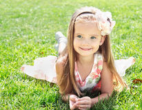 Cute smiling little girl lying on grass Royalty Free Stock Images