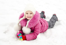 Cute smiling little girl lying on snow in winter day Royalty Free Stock Photography