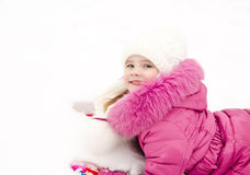 Cute smiling little girl lying on snow in winter day Royalty Free Stock Photos