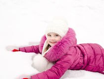 Cute smiling little girl lying on snow in winter day Stock Image