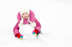 Cute smiling little girl makes snowman in winter day. Outdoor Royalty Free Stock Image