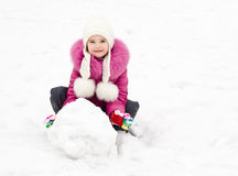 Cute smiling little girl makes snowman in winter day Royalty Free Stock Photography